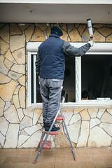 Fenstermonteur dichtet ein Fenster mit Montageschaum ab