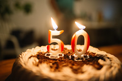a chocolate birthday cake with cream filling and candles has a number fifthy on it