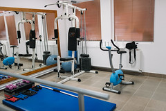 A gym hospital room interior with all the workout machines and a mirror