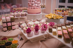 a whole room filled with Tables filled with different type of sweets and cookies all themed pink color