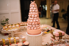 a pile type cake made of small cookies displayed around other cookies on a table in a resturant