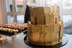 chocolate layered stiff cake on display with cookies in the background