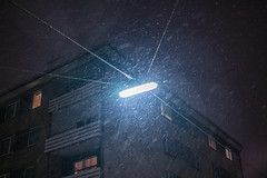 Hard winter with heavy snowfall at night illuminated by a street lamp