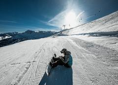 Snowboarder sitting on the snow in ski resort Vars, France