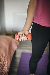Junge Frau hält eine Hantel in der Hand während ihres Trainings