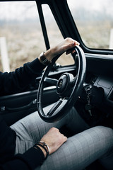 A fashionable man behind a steering wheel