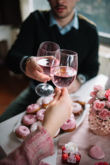 Boyfriend and girlfriend drinking wine. Pink colors for Valentine day