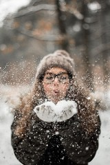 Woman blowing snow outdoors - Credit to https://homegets.com/