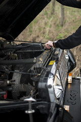 Man taking a look under the hood of a cross country vehicle