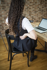 A young woman having back pain while sitting at the desk in her office