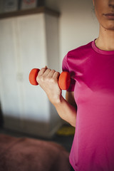 A young woman exercising with a dumbbell