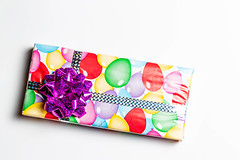Gift with a bow in multicolored paper on a white background