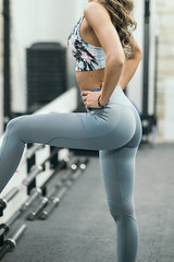 Beautiful body and legs of blonde woman in gym closeup.