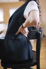 Junge Frau hat Rückenschmerzen während sie in ihrem Büro sitzt