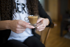 Close-up of a cup of creamy coffee in a young woman's hands