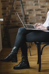 Young female entrepreneur working on her laptop while holding it on her lap