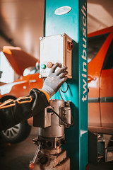 Technician's hand is controlling the lifting button on the car closeup