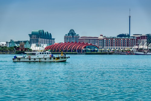 Singapore harbour with boat and view of the resorts and casinos on Sentosa island