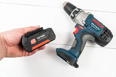 Accu Drill with battery in the hand above white background