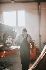 Old worker in a car workshop