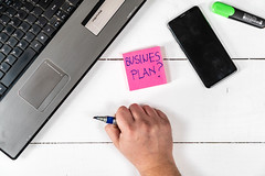 Business Plan concept with lap top hand and mobile phone on the table