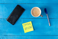 Coffe Break concept with cup of Coffee and Mobile Phone on the table