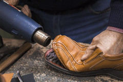 Cobbler heating the glue while gluing the sole to the shoe