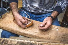 Schoemaker making a sole of a Serbian traditional Opanak shoe