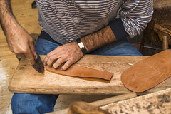 Shoemaker cutting leather for traditional shoes