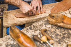 Shoemaker driling holes in leather