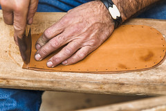 Shoemaker cutting leather to form