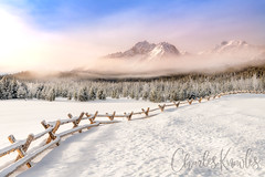 Fence leads through a snow field towards the Sawtooth Mountains