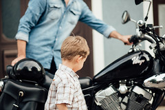 Dad teaching son to ride a motorycle.