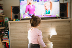 Little girl standing and watching television at home