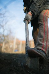 A old man digs the ground with a shovel closeup