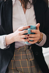 Closeup of vintage business woman holding a blue cup of coffee.