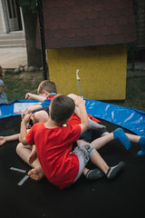 Young boys jumping on the trampoline in backyard