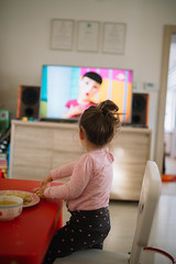 Little girl watching television at home