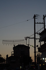 Black silhouette of cityscape in sunset light.