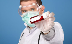 Doctor holding blood sample tube on blue background