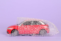 Red car packed in bubble wrap