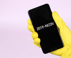 Hands in yellow rubber gloves holding mobile phone with 2019-NCOV text