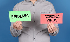 Man holding a green banner with a word epidemic and red banner with Coronavirus text on blue background