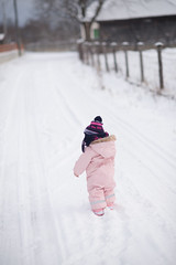 Baby walking on a road with snow.