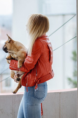Blonde girl in red jacket holding her dog on balcony.