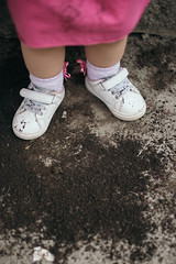 Baby girl's legs covered with soil