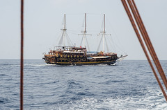 Old wooden sailboat on blue sea.