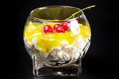 A glass of cottage cheese dessert with fresh kiwano and red currants on a black background