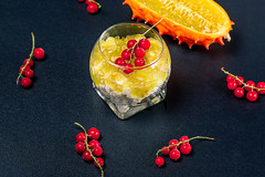 Diet food-cottage cheese with kiwano and red currant on a dark background