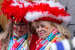Carnival in Germany: woman with colorful costume, red-white feather hat and heart-shaped cologne coat of arms